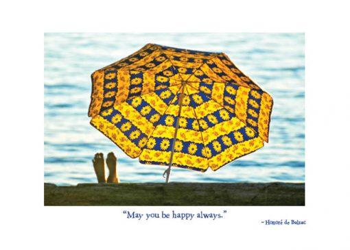 sunbather on beach under colorful umbrella
